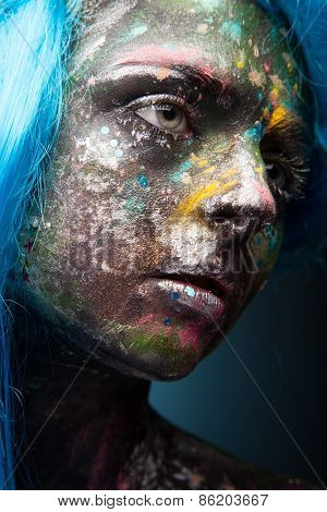 Blue hair. Woman with face art and body art.