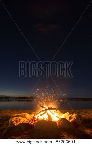 Sparking camp fire beside lake under a starry sky.