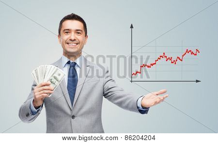 business, people, success and finances concept - smiling businessman with american dollar money and growing chart over gray background