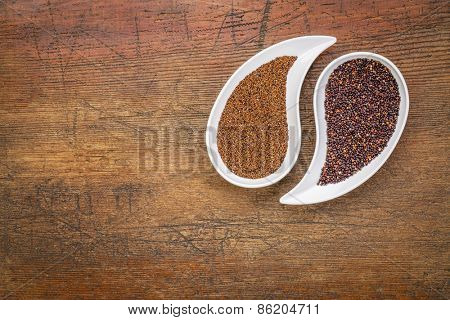 kaniwa and black quinoa  gluten free grains on on teardrop shaped bowls against rustic wood with a copy space