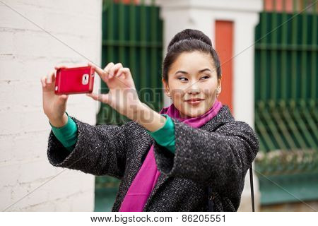 Young beautiful woman tourist taking pictures on mobile phone on the background spring street