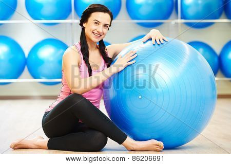woman instructor portrait with fitness ball during pilates stretching exercises in sport club