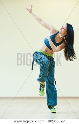 female zumba instructor doing dancing exercises in sport club