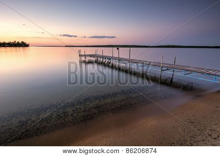 Sandy beach and dock beside lake at sunset. Minnesota, USA
