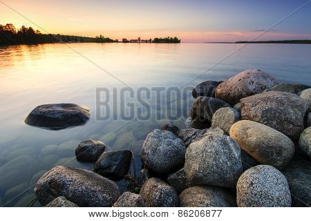 Large boulders on lake shore at sunset. Minnesota, USA