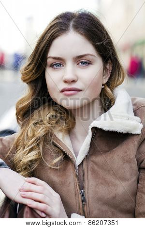 Portrait close up of young beautiful woman, on background spring street