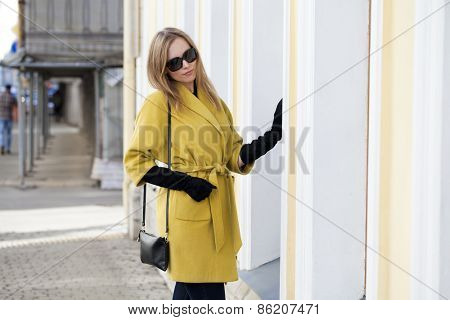 Young beautiful woman in a yellow coat standing at the wall of the building