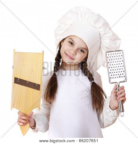 Beautiful little girl in a white apron and holding a wooden grater shredder vegetables, isolated on white background