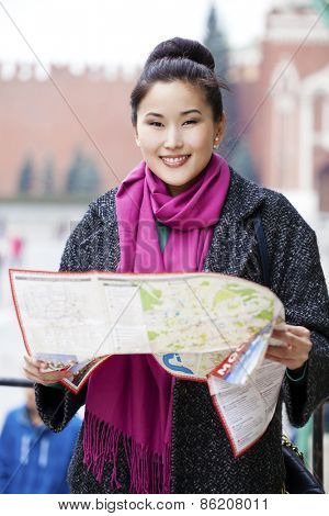 Young beautiful asian girl holding a tourist map of Moscow, Russia
