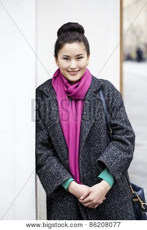 Asian beautiful woman in stylish gray coat on a background of spring street