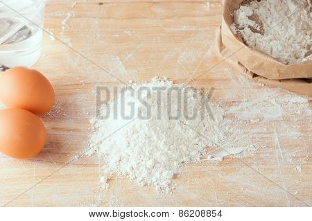 Flour And Eggs On Wooden Board