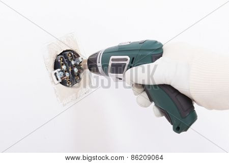 Electrician replacing old socket with cordless drill/driver
