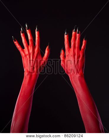 Red devil hands with black nails for Halloween theme, studio shot on black background