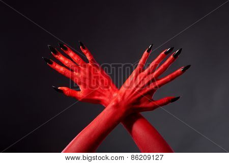 Crossed red devil hands with black nails, studio shot on black background