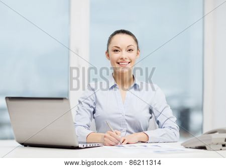 business, technology and communication concept - smiling businesswoman with phone, laptop and files in office