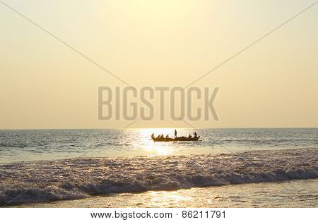 Fishermen in a boat floating in the ocean on the reflection of the sun