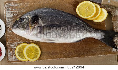 Fresh Sea Bream With Lemon On  Wooden Cutting Board