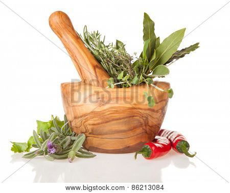 Wooden mortar filled with fresh herbs, isolated on white background
