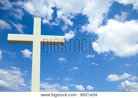 White Christian cross in front of a cloudy sky with copyspace