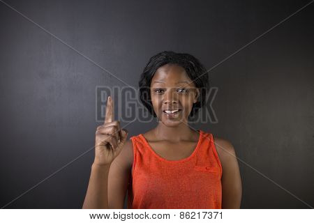 South African Or African American Woman Teacher Hand Up On Chalk Black Board Background