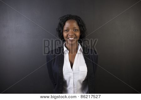 South African Or African American Woman Teacher Or Student Against A Dark Blackboard Background