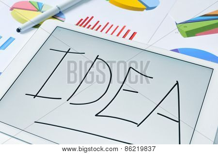 the word idea on the screen of a tablet computer placed on a table full of different colorful graphs