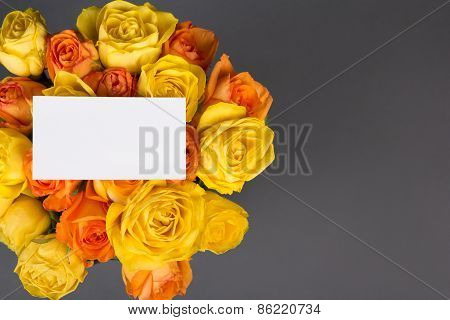 Blank Gift Card And Beautiful Bouquet Of Orange And Yellow Roses Over Grey