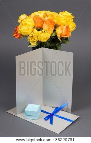 Blank Gift Card, Bouquet Of Orange And Yellow Rose Flowers And Gift Box Over Grey
