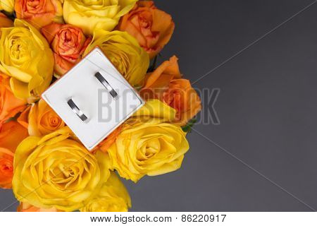 Bouquet Of Orange And Yellow Rose Flowers And Wedding Rings In Gift Box Over Grey