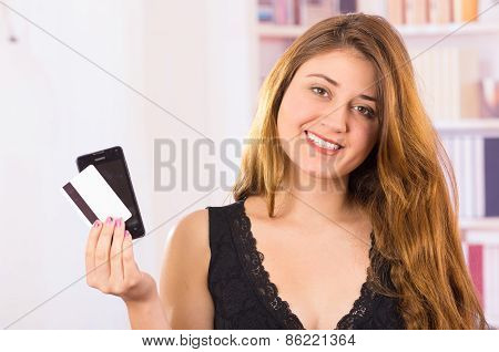 modern beautiful young woman holding cell phone and credit card