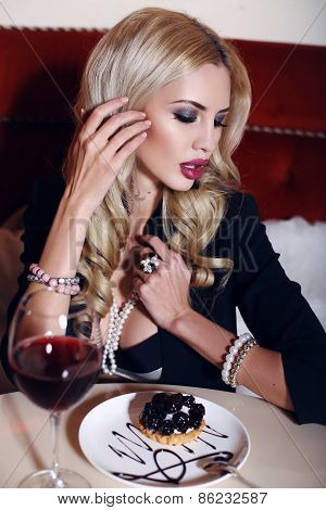 Blond Woman Sitting In Cafe With Glass Of Wine And Dessert