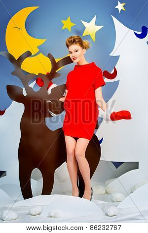 Attractive young woman in festive red dress posing in Christmas decorations. Fashion shot.