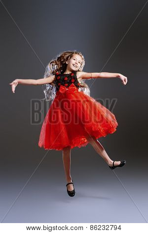 Cute teen girl in a beautiful festive dress dancing at studio. Beauty, children's fashion. Studio shot.
