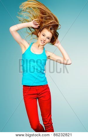 Pretty girl teenager jumping at studio expressing happiness. Hair care, healthy hair.