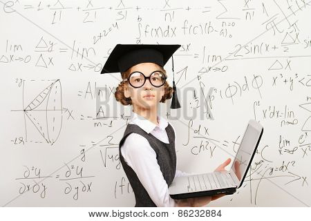 Smart schoolgirl in big glasses and academic hat performs the task at the blackboard with a laptop. Education.