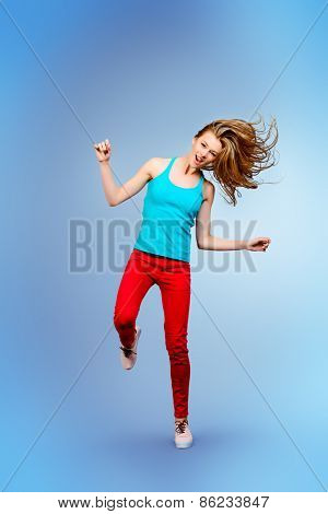 Pretty girl teenager jumping at studio expressing happiness.
