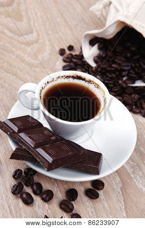 sweet hot food: black coffee with dark chocolate and coffee beans in bag on wooden table