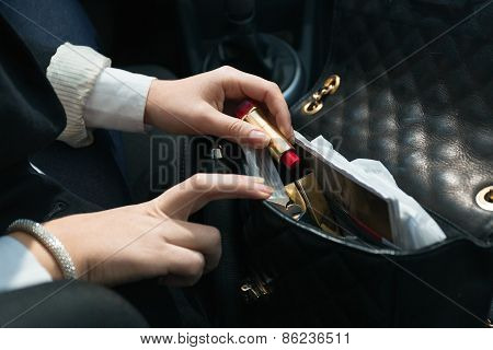 Woman Sitting In Car And Taking Lipstick Out Of Handbag