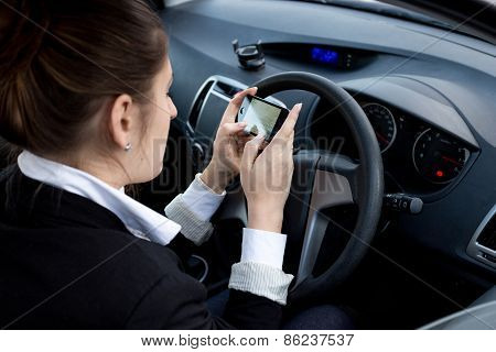 Businesswoman Using Smartphone While Driving Car