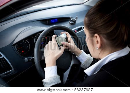 Businesswoman Typing Text On Smartphone At Car