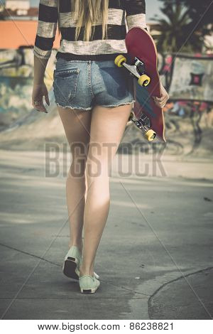 Beautiful and sexy street girl walking with her skateboard under her arms
