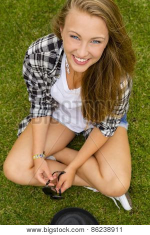 Happy and beautiful teenage girl sitting on the grass