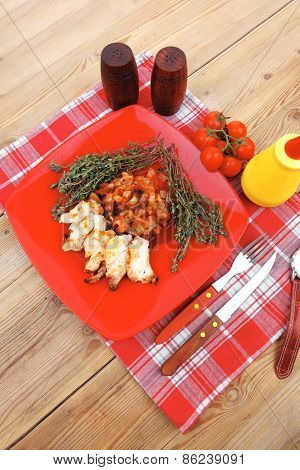 meat grilled chicken fillet with salad and tomatoes on red plate over wooden table with cutlery on lunch time