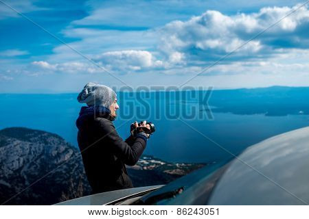 Photographer with car on the top of mountain
