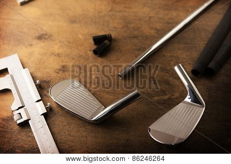 Assembling golf clubs or golf club making. Iron head, steel shaft, ferrule and grip on a well used work bench. Shot in impression-like surreal color with low key shadows. Shallow depth of field.