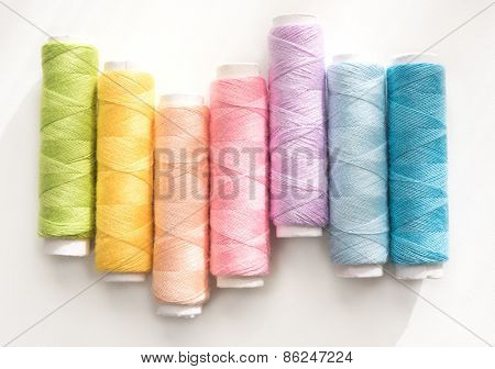 Spring colors. Light colored sewing threads on a white table with warm spring sunlight by the natural by-the-window spring sunlight lighting .