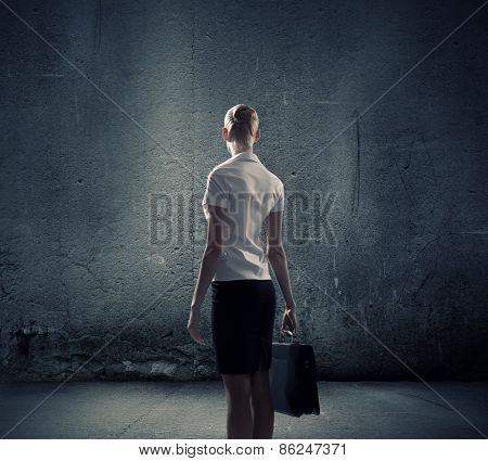 Rear view of businesswoman looking at blank cement wall