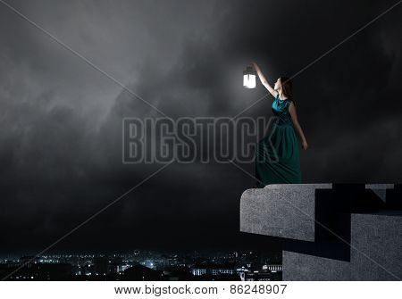 Young woman in green dress with lantern in darkness