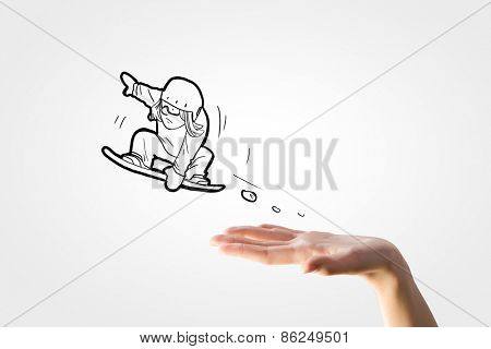 Close up of human hand and caricature of jumping snowboarder
