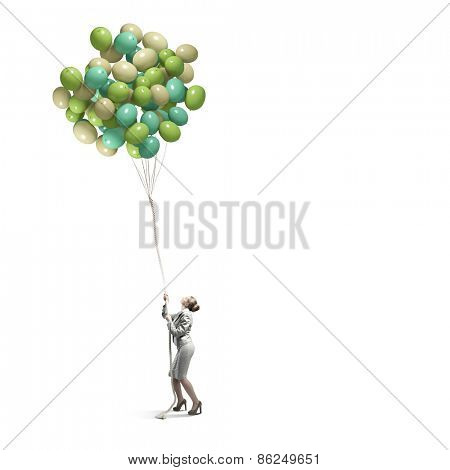Young businesswoman pulling bunch of colorful balloons